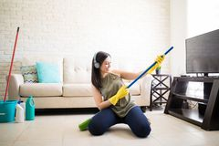 Woman enjoying playing with broom. Playful young woman playing guitar with broom and listening to music over headphones Royalty Free Stock Photography