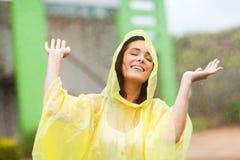 Woman enjoying rain. Pretty young woman enjoying the rain outdoors royalty free stock image