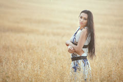 Woman is enjoying the rain in the field. Woman enjoys the rain in a wheat field. Rain drops fall on it and it gets wet Royalty Free Stock Image
