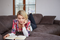Woman enjoying reading a book at home lying on the Royalty Free Stock Photo