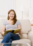 Woman enjoying reading a book in livingroom Stock Image