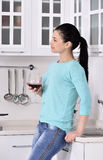Woman enjoying red vine in the kitchen Stock Photo