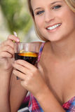 Woman enjoying a refreshing drink. Closeup of a young woman enjoying a refreshing drink on a warm summer's day Royalty Free Stock Photos