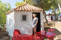 Woman enjoying relaxing summer vacations in authentic vintage bungalow of camping village under mediterranean pine trees Stock Photography