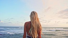 Woman enjoying sea blonde hair blowing in wind Travel Lifestyle vacations and harmony with nature relaxing concept rear. View stock footage