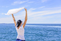 Woman enjoying the sea breeze holding a silk handkerchief waved by the wind against the sea. Royalty Free Stock Photography