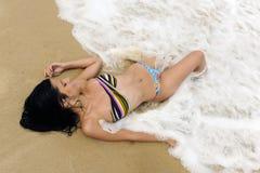 Woman enjoying the sea lying on seashore Royalty Free Stock Photography