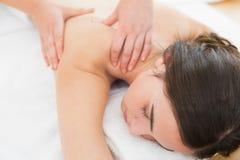 Woman enjoying shoulder massage at beauty spa royalty free stock photos