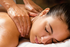 Woman enjoying shoulder massage in spa. Royalty Free Stock Photos