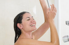 Woman enjoying a shower. Woman taking a shower enjoying water splashing on her royalty free stock photos