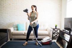 Woman enjoying singing using vacuum cleaner tube as mike. Cheerful young woman enjoying solo singing with vacuum cleaner while cleaning house Stock Photos
