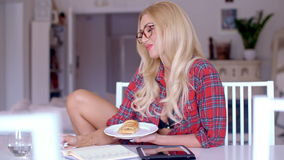 Woman enjoying a snack while working at home stock video