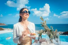 Woman enjoying some good food on beach house party. With the sea and a pool royalty free stock photos