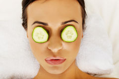 Woman enjoying spa, having cucumber on eyes. Woman in spa with cucumber on eyes royalty free stock photography