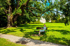 Woman enjoying spring in the park. Young woman reading book on the bench smiling and happy. Pretty young woman enjoying spring in the park Stock Photography