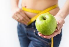 Woman enjoying successful weight loss. Out of focus woman measuring her waistline and showing fresh green apple in hand Royalty Free Stock Photo