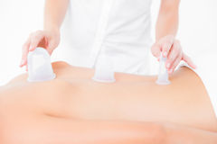 Woman enjoying a suction back massage. Close up view of woman having a suction massage at the health spa Stock Photo