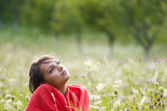 Woman enjoying summer. A portrait of a young woman, sitting in a field full of wild flowers as she enjoys a summer day stock photos