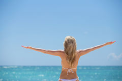 Woman enjoying summer by the ocean Royalty Free Stock Image