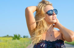 Woman enjoying the summer sun. Woman in sunglasses with her head tilted towards the sky enjoying the summer sun out in the open countryside Stock Photos