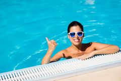 Woman enjoying summer vacation happiness and relax in swimming pool. Cheerful woman on summer vacation doing thumbs up success gesture in swimming pool Stock Photos