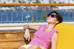 Woman enjoying the summer vacation laying on a sunbed in a sea bar Stock Photography