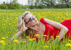 Woman enjoying sun in a meadow Royalty Free Stock Photo