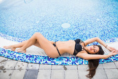 Sexy Woman in bikini enjoying sunbath on the pool edge on a sunny day, Summer vocation Royalty Free Stock Photos