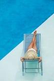 Woman enjoying on sunbed at swimming pool Stock Image