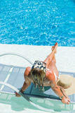 Woman enjoying on sunbed at swimming pool Royalty Free Stock Photo