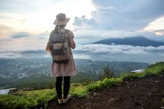 Woman enjoying sunrise from a top of mountain Batur, Bali, Indonesia stock photos