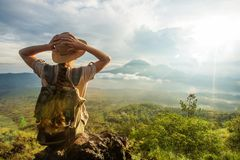 Woman enjoying sunrise from a top of mountain Batur, Bali, Indonesia royalty free stock photography