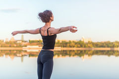 Woman enjoying sunset with arms outspread and face raised in sky Royalty Free Stock Photography