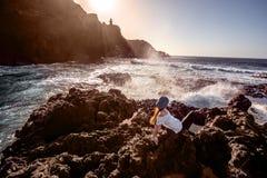 Woman enjoying sunset on the rocky coast Stock Photos