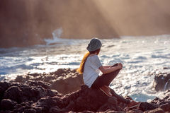 Woman enjoying sunset on the rocky coast Royalty Free Stock Photo