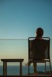 Woman enjoying sunset sitting on balcony Stock Images