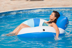 Woman enjoying a swimming pool Stock Image