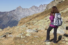 Woman enjoying the Swiss Alps during hiking in autumn. Woman hiking on Swiss Alps watching the mountain landscape Royalty Free Stock Image