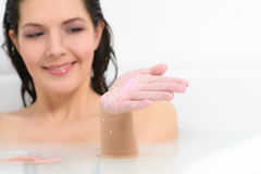 Woman enjoying a therapeutic aromatherapy bath. Woman enjoying a rejuvenating therapeutic aromatherapy bath at a spa soaking in the warm soapy water pouring bath Stock Images
