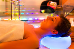 Woman enjoying therapy in spa with color therapy. Colorful lights stimulating the psyche stock images