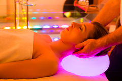 Woman enjoying therapy in spa with color therapy. Colorful lights stimulating the psyche stock photos