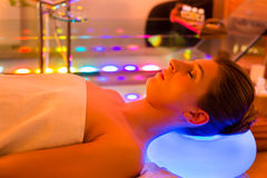 Woman enjoying therapy in spa with color therapy. Colorful lights stimulating the psyche royalty free stock photo