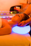 Woman enjoying therapy in spa with color therapy. Colorful lights stimulating the psyche stock photo