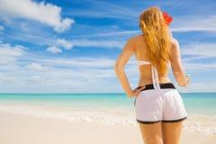 Woman enjoying tropical beach relaxing joyful in summer by tropical blue water Stock Photo