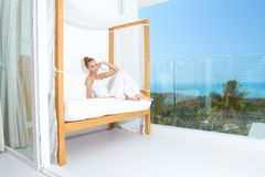 Woman enjoying tropical luxury. Woman relaxing on a canopied seat on a glass fronted patio overlooking the ocean enjoying tropical luxury Royalty Free Stock Images