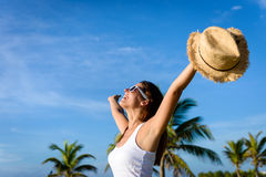 Woman enjoying tropical vacation travel and freedom. Blissful woman on tropical caribbean vacation raising arms to the sky. Freedom and travel concept. Brunette Stock Photography