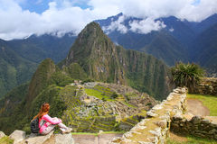 Woman enjoying the view of Machu Picchu citadel in Peru. In 2007 Machu Picchu was voted one of the New Seven Wonders of the World Stock Photos