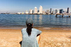 Woman enjoying the view of the San Diego bay and skyline while s. Back view of a woman sitting on beach and looking out into bay of San Diego, California royalty free stock images