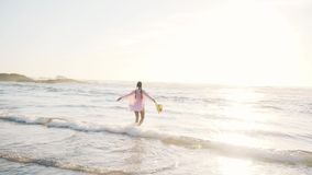 Woman enjoying a walk along the beach. During her summer vacation stock footage