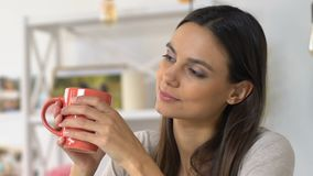 Woman enjoying warm beverage in cozy home atmosphere, relaxation and harmony. Stock footage stock video